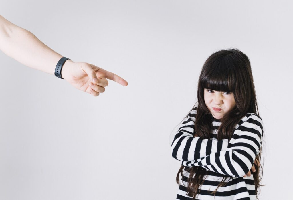 Uma criança com braços cruzados, aparentando irritação ou desaprovação, com a mão de um adulto apontando para ela