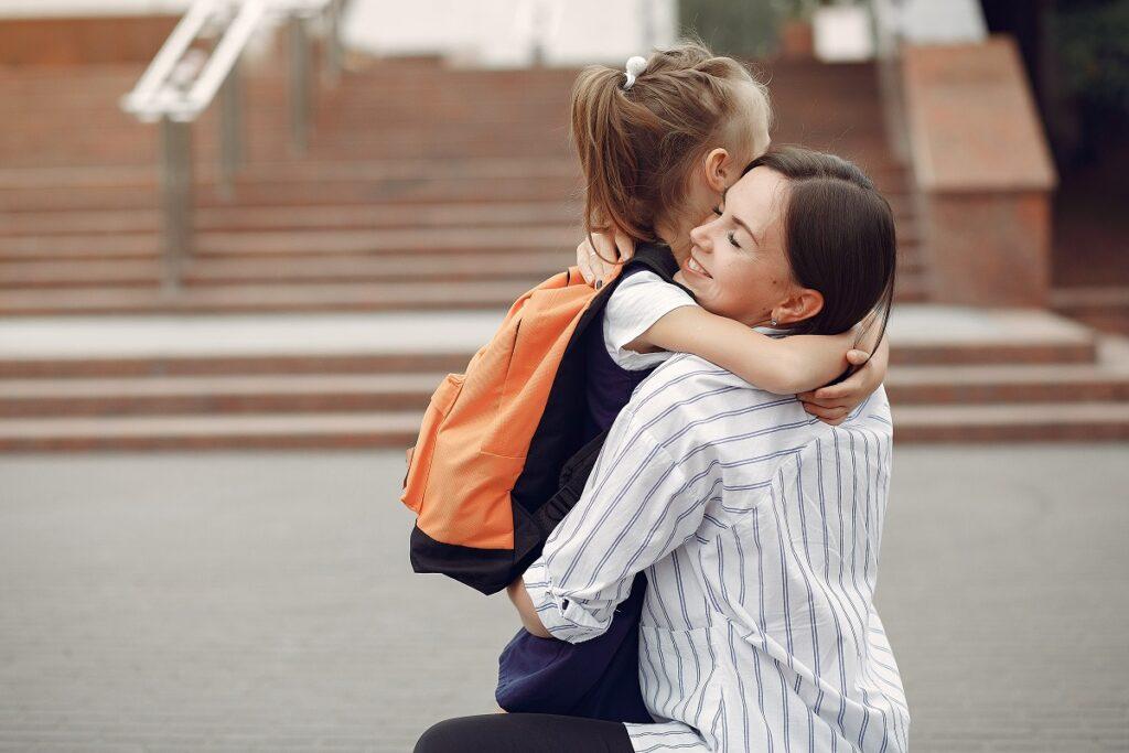 Uma mãe abaixada, abraçando afetuosamente sua filha. A criança possui uma mochila nas costas.